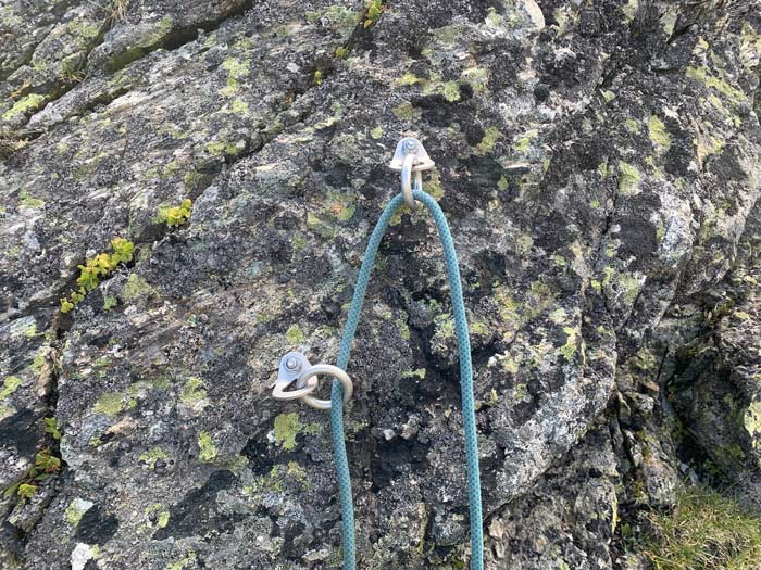 Das Bild zeigt eine korrekt eingerichtete Abseilstelle mit zwei einzelnen Bohrhakenlaschen mit Ring im Granit.